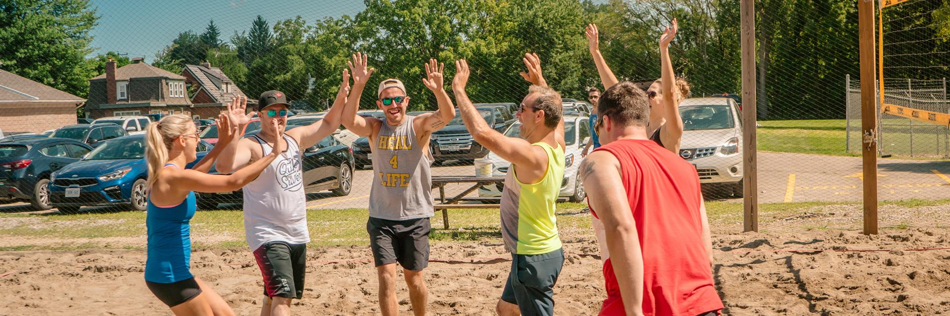 Beach volleyball team giving a high five.