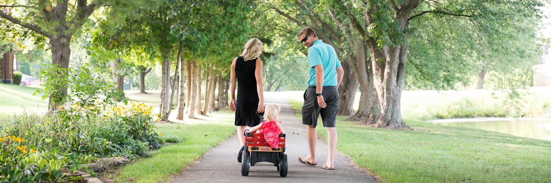 Two parents walking down a tree lined path, pulling their child in a wagon.