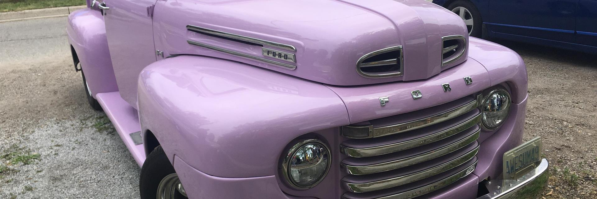a purlple classic truck parked on the grass at a car show in chatham-kent