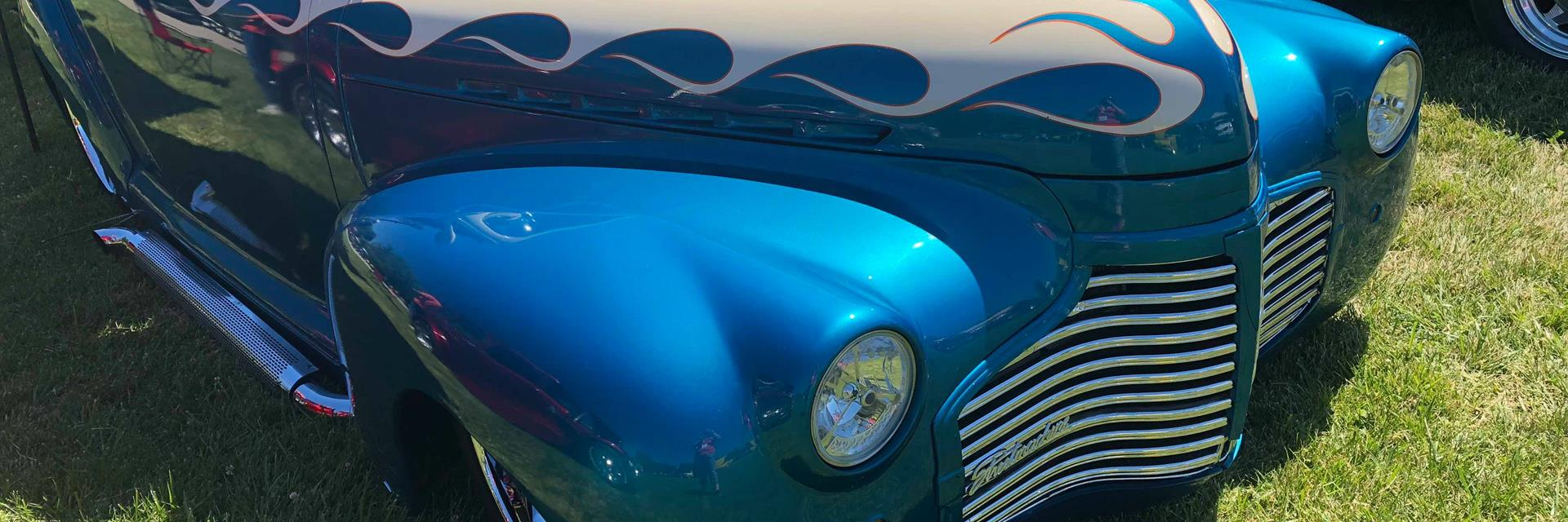 a blue and silver classic car on display at a classic car show in chatham-kent